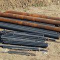 Трубы разного диаметра лежат на земле на строительной площадке